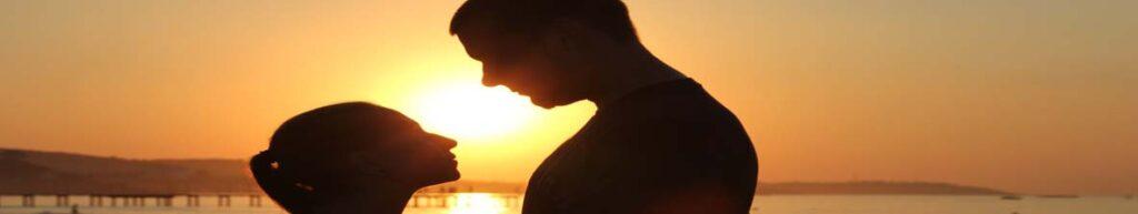 Eyaculación retardada pareja intimando al atardecer con puesta de sol de fondo